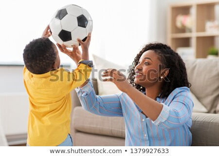 mother and baby playing with soccer ball at home Stock photo © dolgachov