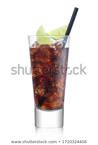 Cuba Libre Cocktail in glass with ice cubes and slice of lime with black straw and stirrer on white. Stock photo © DenisMArt