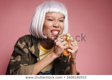 Image of wild asian girl wearing white wig eating big burger Stock photo © deandrobot