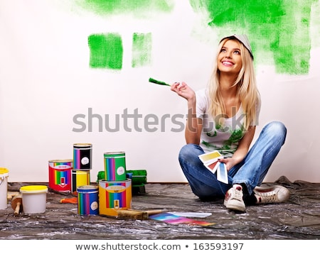 Young woman holding a paint can and paintbrushes Stock photo © photography33