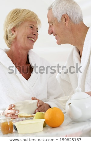senior couple in bathrobe sitting on a bed having breakfast stock photo © photography33