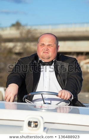 Overweight man in a tuxedo at the helm of a pleasure boat Stock photo © Discovod