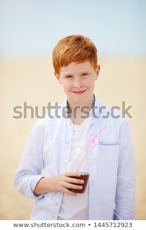 boy with red hair is thirsty and drinks with a straw  Stock photo © meinzahn