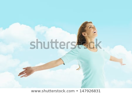 attractive blond woman against blue cloudy sky stock photo © nejron