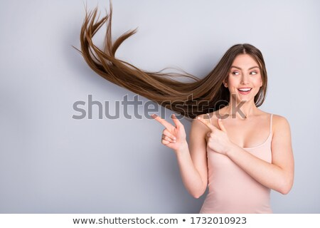 beautiful young woman with her hair in the wind, finger in the air, looking up Stock photo © alexandrenunes