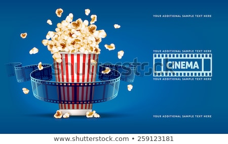 popcorn for cinema and movie film tape on blue background stock photo © loopall