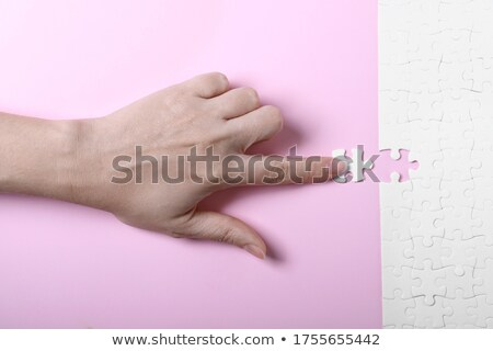 female hand putting a missing piece into jigsaw puzzle stock photo © stevanovicigor