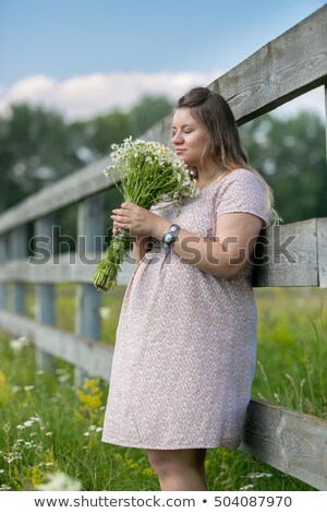 Portrait of a pregnant woman smelling flower Stock photo © deandrobot