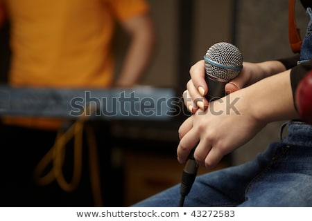 Microphone in hand of vocalist girl. keyboard player in out of focus Stock photo © Paha_L