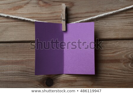 Stock photo: Purple Greetings Card Pegged to String on Wood Background
