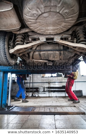 inside a garage - two mechanics working on a car, changing wheel Stock photo © lightpoet
