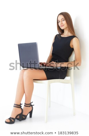 Smiling happy businesswoman in black dress sitting on the chair Stock photo © deandrobot