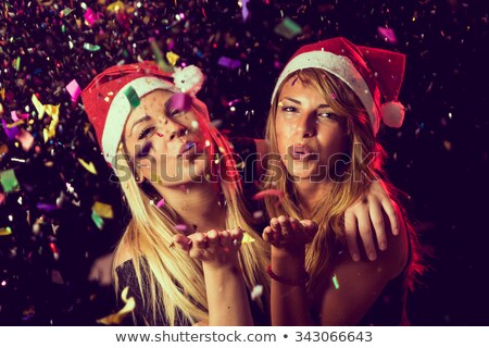 cheerful beautiful young woman in santa claus hat dancing stock photo © deandrobot