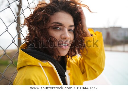 Serious african curly young woman wearing yellow coat Stock photo © deandrobot