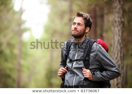portrait of smiling man with backpack walking in the forest stock photo © wavebreak_media