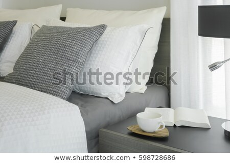 Book And Lamp On Night Table In Hotel Room Stock Photo