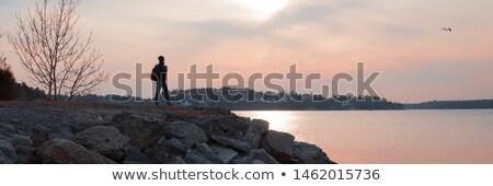 beautiful girl standing on rocky shore Stock photo © svetography