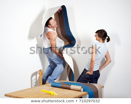 Smiling man struggling with wallpaper Stock photo © IS2