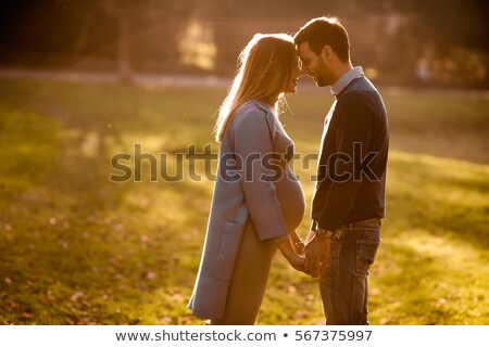 Stock photo: Pregnant woman and man posing at autumn park
