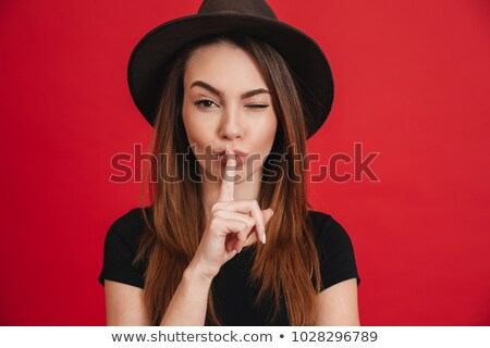 Beautiful pretty woman posing isolated showing silence gesture. Stock photo © deandrobot