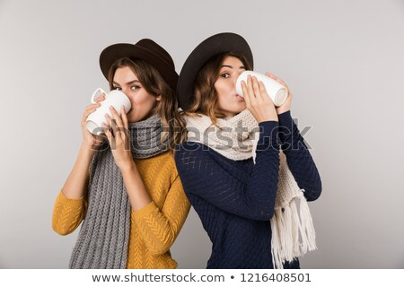 Image of two brunette women wearing hats and scarfs drinking hot Stock photo © deandrobot