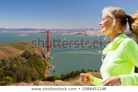 woman with earphones running over san francisco Stock photo © dolgachov