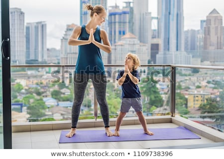 Mom and son are practicing yoga on the balcony in the background of a big city. Sports mom with kid  Stok fotoğraf © galitskaya