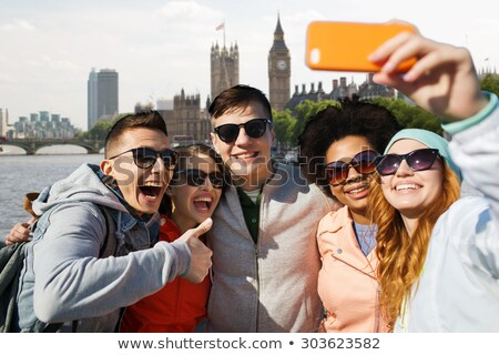 happy friends over houses of parliament in london Stock photo © dolgachov