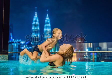 Mother and son in outdoor swimming pool with city view at night Stock photo © galitskaya