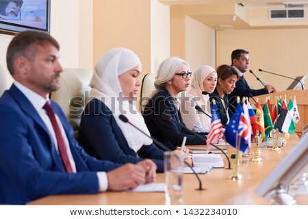 Row of young intercultural delegates in formalwear sitting by table Stock photo © pressmaster