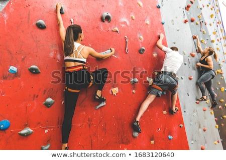 Jeune femme escalade gymnase mur Photo stock © dolgachov