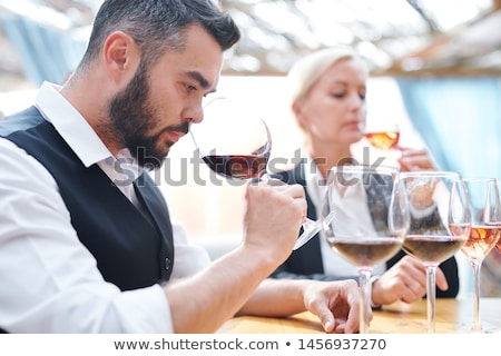 Young sommelier feeling smell of red wine while holding wineglass by his nose Stock photo © pressmaster