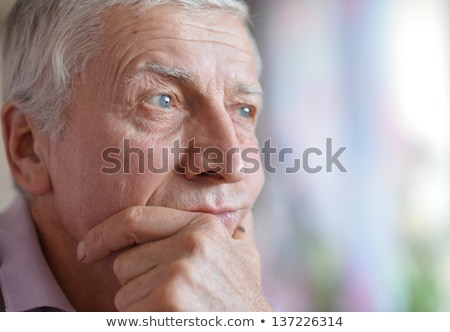 close up of sad senior man thinking stock photo © dolgachov