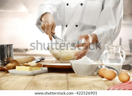 Female chef mixing ingredients of cake in bowl Stock photo © Kzenon