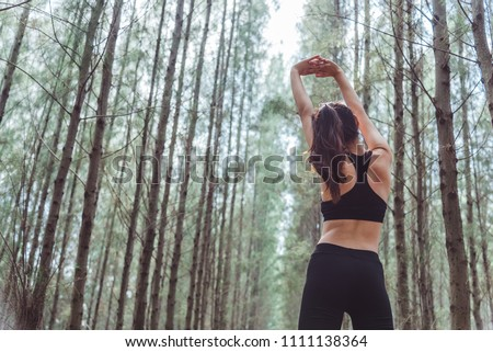 Young woman stretching and breathing fresh air in middle of fore Stock photo © boggy