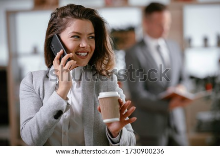 Portrait of pretty young Caucasian businesswoman talking on mobile phone standing in modern office.  Stock photo © wavebreak_media