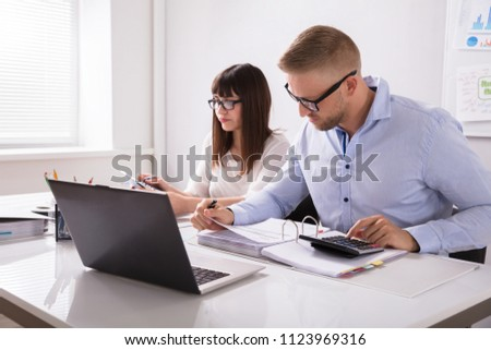 Two Businesspeople Calculating Bills In Office Stock photo © AndreyPopov