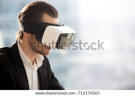 Businessman looking through Virtual Reality glasses Stock photo © ra2studio
