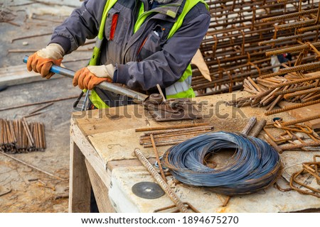 Worker Using Tools To Bend Steel Rebar At Construction Site Stock photo © feverpitch