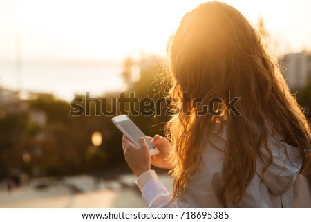 Beautiful woman using her phone in the city in autumn Stock photo © Kzenon