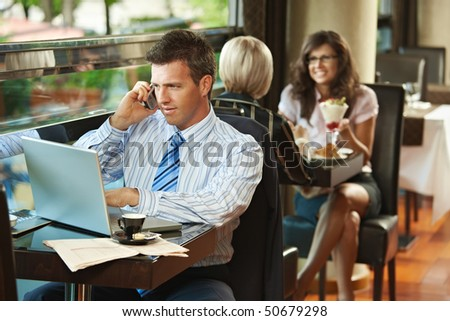 Photo of businessman talking on cellphone and using laptop in ap Stock photo © deandrobot