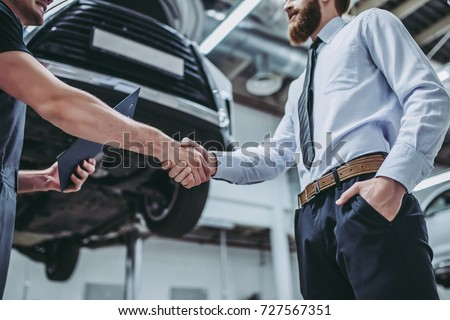 auto mechanic and man shaking hands at car shop Stock photo © dolgachov
