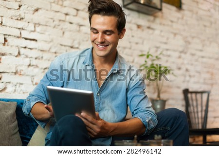 Image of young laughing businessman holding and using laptop Stock photo © deandrobot