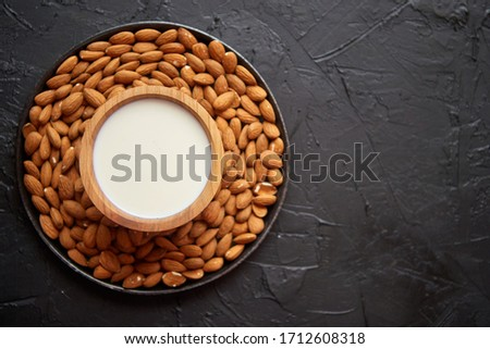 Composition of almonds seeds and milk, placed on black stone background. Stock photo © dash