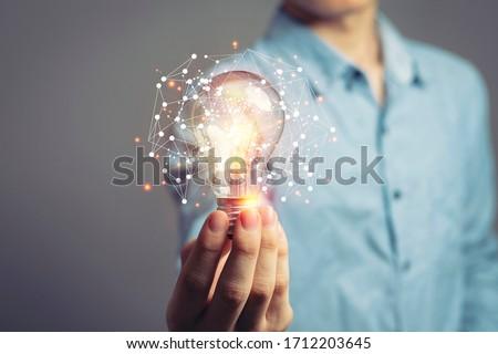 üzletember tart villanykörte új üzlet villanykörte Stock fotó © ra2studio