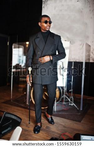 Businessman in black suit holding walking cane stick Stock photo © ia_64