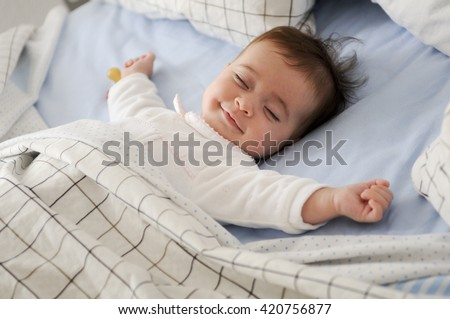 happy cute baby lying on white sheet stock photo © lopolo