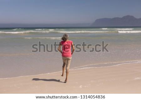 Rückansicht Senior Frau läuft Strand Sonnenschein Stock foto © wavebreak_media