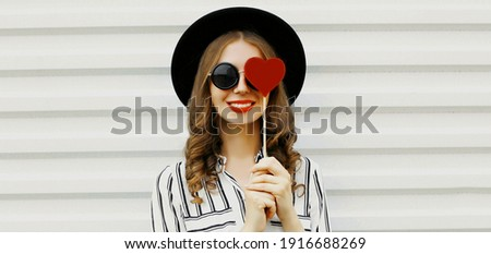 smiling teenage girl covering eye with red heart Stock photo © dolgachov