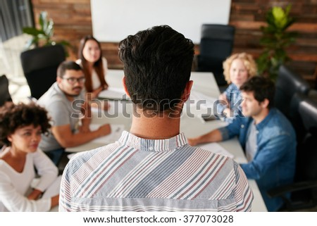 Rear view of standing mixed race business colleagues discussing over chart in modern office Stock photo © wavebreak_media